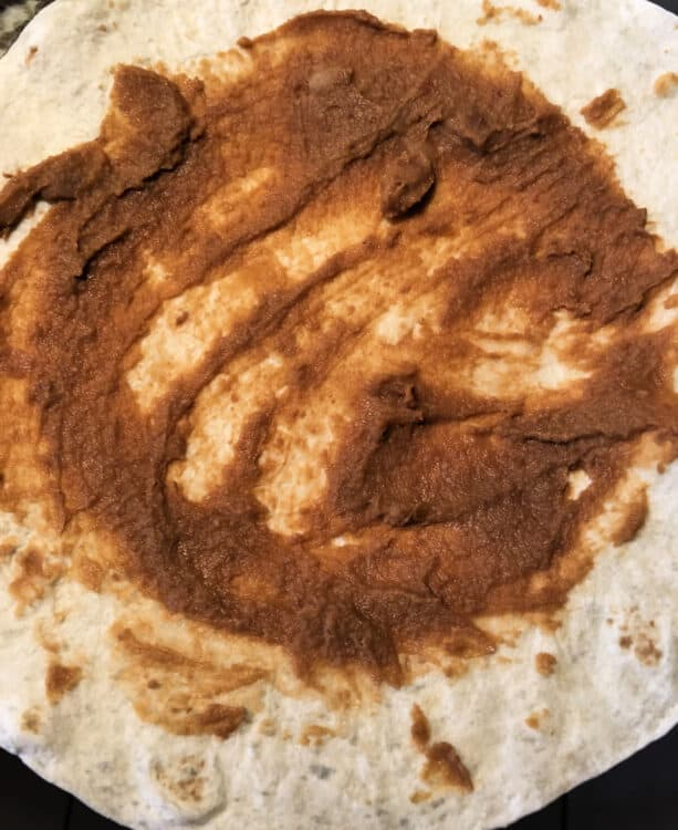 flour tortilla spread with refried beans
