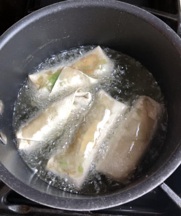 homemade egg rolls starting to cook in oil