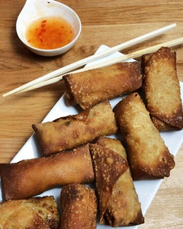 arrangement of homemade eggg rolls on a platter with dipping sauce