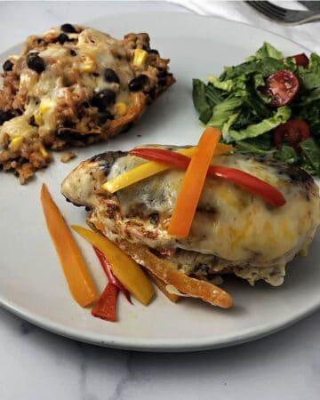 Fajita stuffed chicken on a plate with rice and a salad