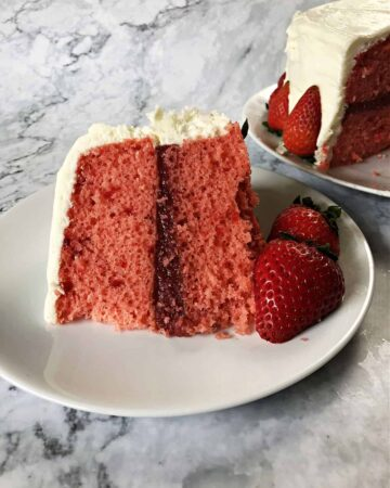 slice of layered cake with strawberry cake filling