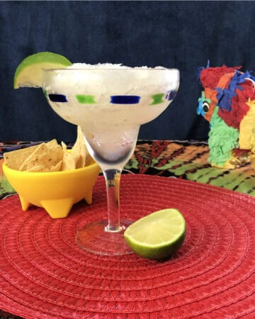 margarita slush in a stemmed glass on a red placemat with chips and a lime