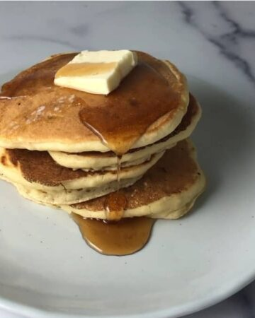 stack of 4 almond milk pancakes with butter and syrup