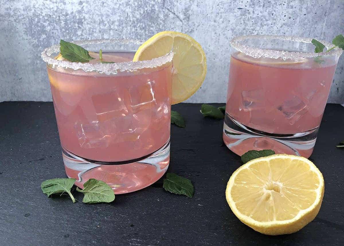 Pink senorita 2 drinks garnished with lemon slices and mint
