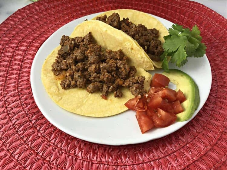 taco meat in small corn tortillas on a small plate