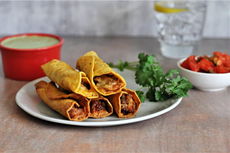 air fried taquitos on a small plate with cilantro and sauces behind