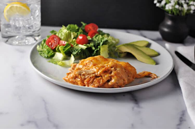 keto chicken taco casserole on a plate with a green salad