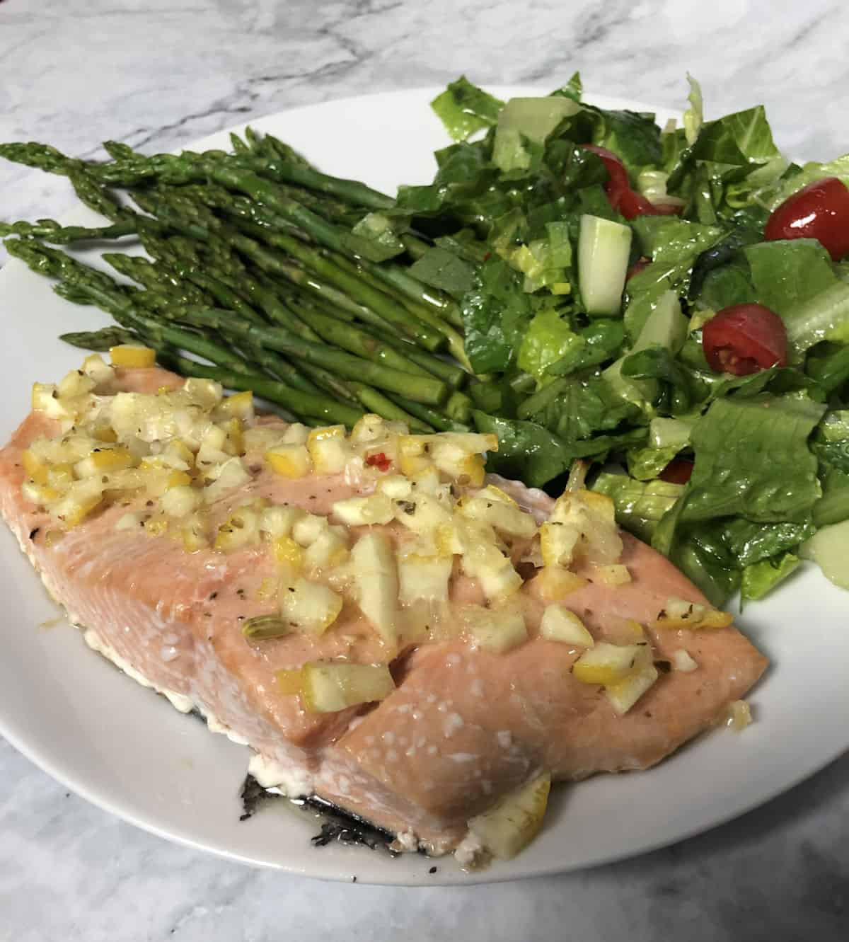 salmon with lemon dressing on a plate with asparagus and salad