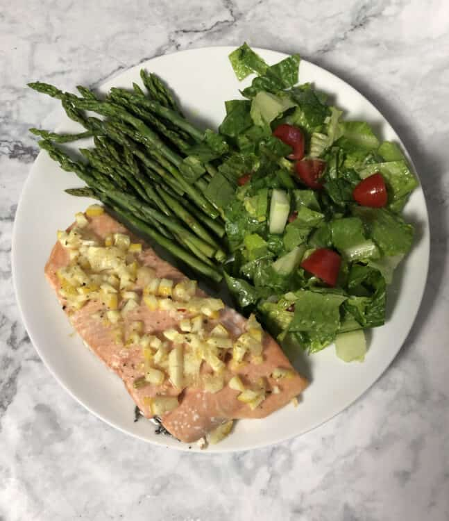 top down of salmon with lemon dressing on a plate with salad and asparagus