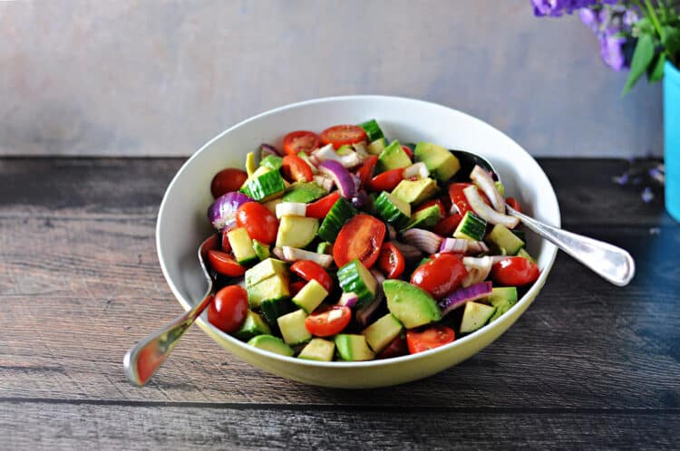 ba;samic cucumber tomato salad in a serving bowl with 2 serving spoons