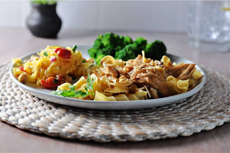 Instant Pot French onion chicken on noodles, broccoli and salad behind on the same plate