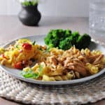 Instant pot french onion chicken with noodles on a plate with broccoli and a salad