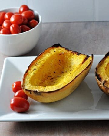 grilled spaghetti squash on a plate with grape tomatoes nearby