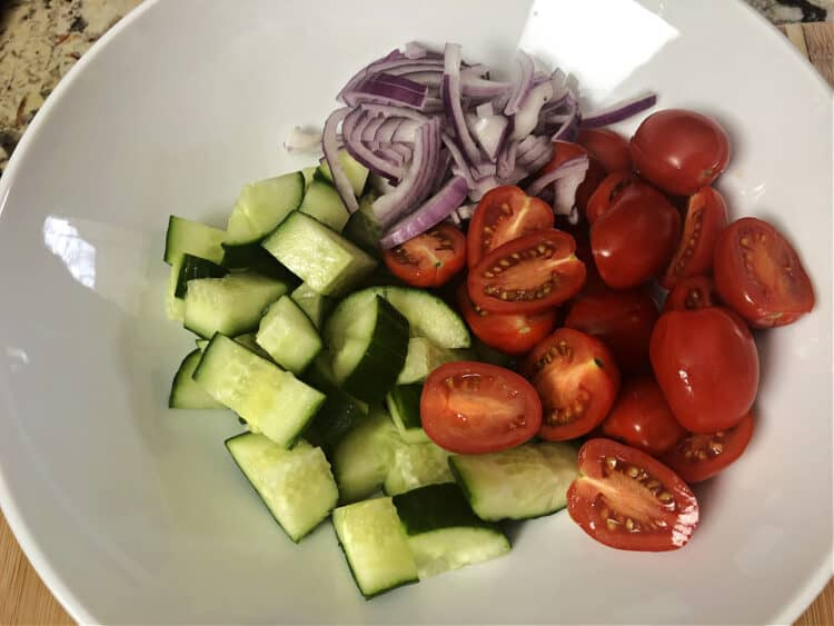 cut up tomatoes, cucumber and red onion in a bowl
