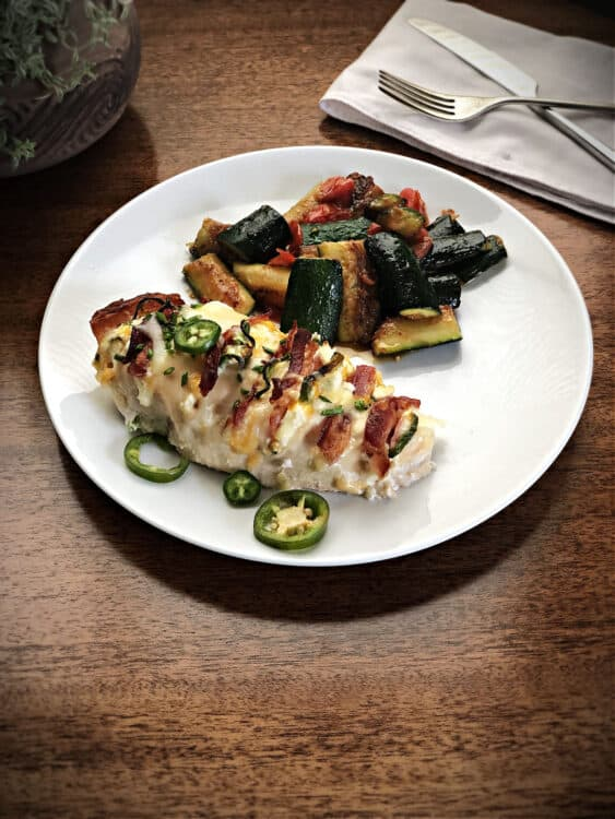 Jalapeno Popper Hasselback Chicken on a plate with zucchini