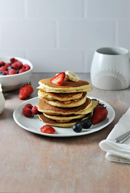 stck of oat milk pancakes on a plate with berries