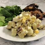 Redskin potato salad on a plate with a green salad and grilled chicken