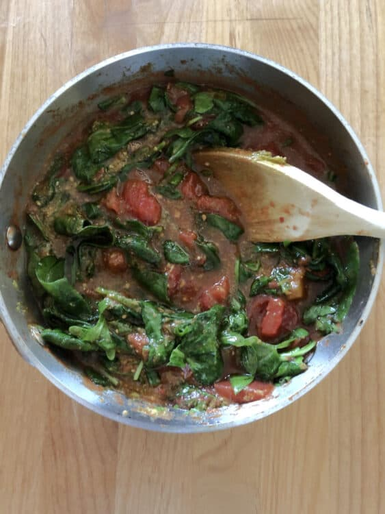 stomato and spinach auce cooking in a saucepan