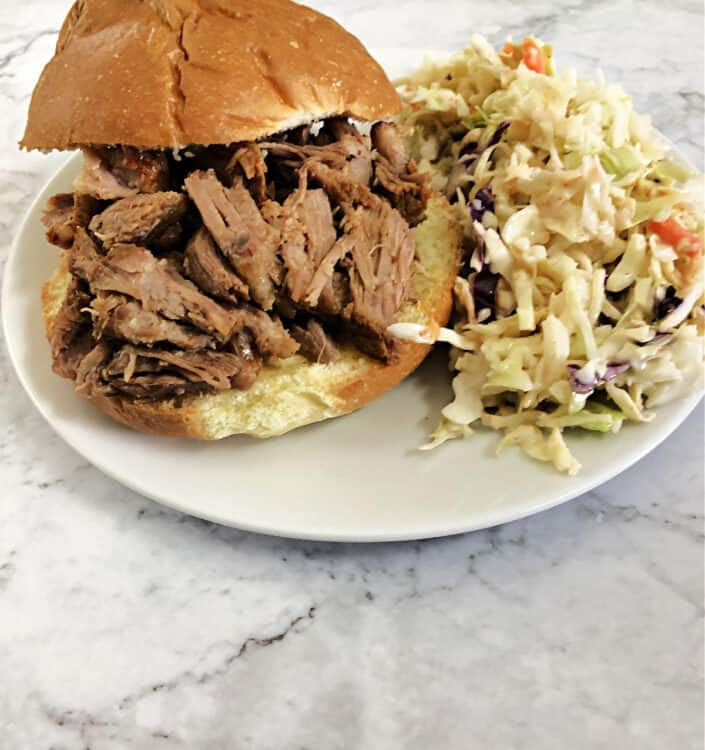 pulled pork sandwich with coleslaw on a small white plate