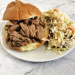 pulled pork on a sandwich bun with coleslaw on a white plate