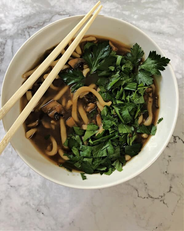 spicy mushroom noodle soup served in a white bowl with chopped frresh herbs on top