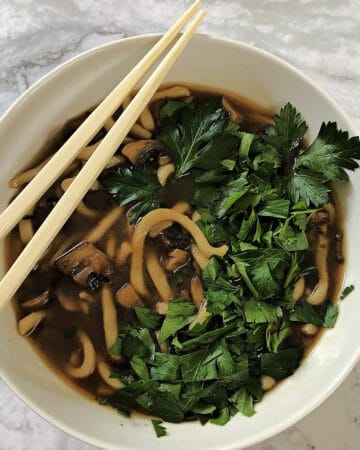 spicy noodle soup with mushrooms and herbs in a white bowl