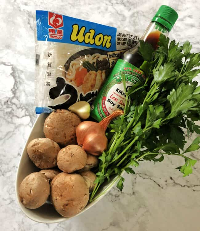 ingredients for soup: mushrooms, noodles, shallot, garlic, soy sauce, fresh herbs