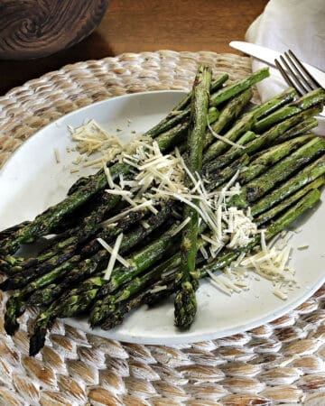 grilled asparagus on a white plate with parmesan cheese sprinkled on top