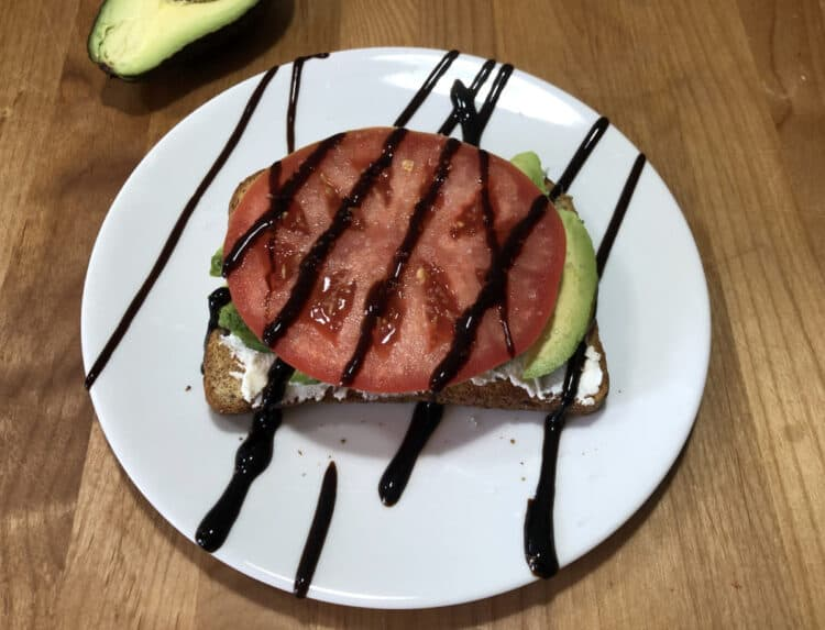 avocado toast with a tomato slice and drizzle of balsamic glaze