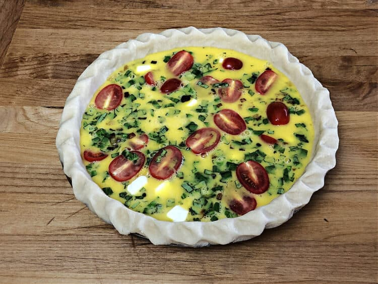 quiche ingredients in a pie plate ready to bake