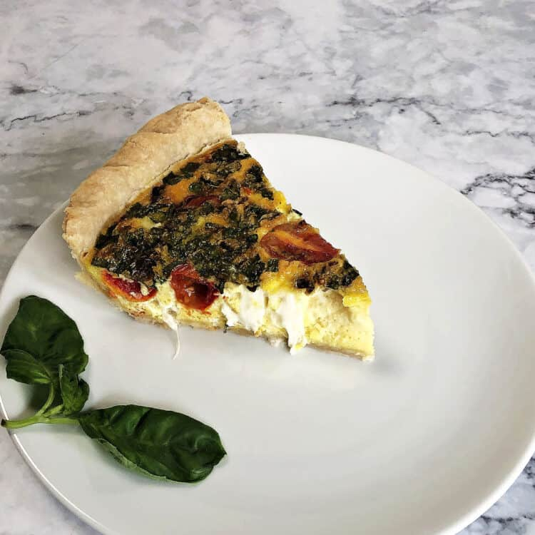 slice of caprese quiche on a white plate with a sprig of basil