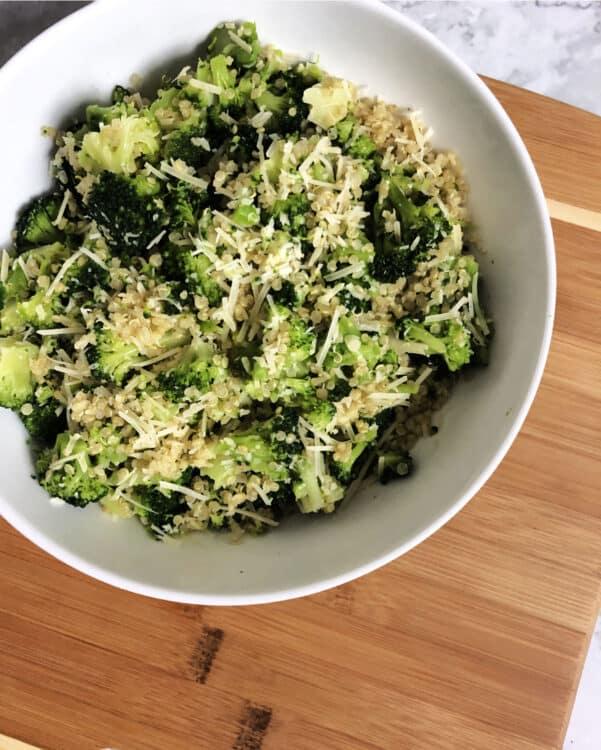 quinoa broccoli parmesan in a white bowl on a cutting board