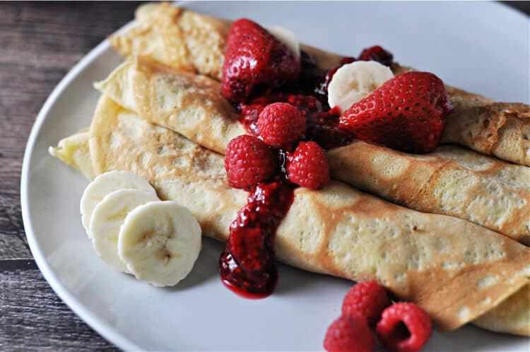 almond milk crepes close up showing fresh fruit and berry sauce