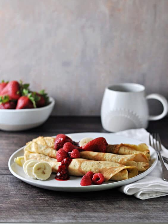 3 crepes on a plate with fruit and berry sauce