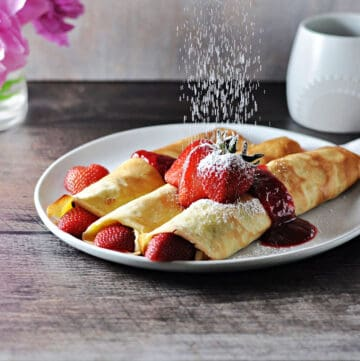 almond milk crepes with fruit being dusted with powdered sugar