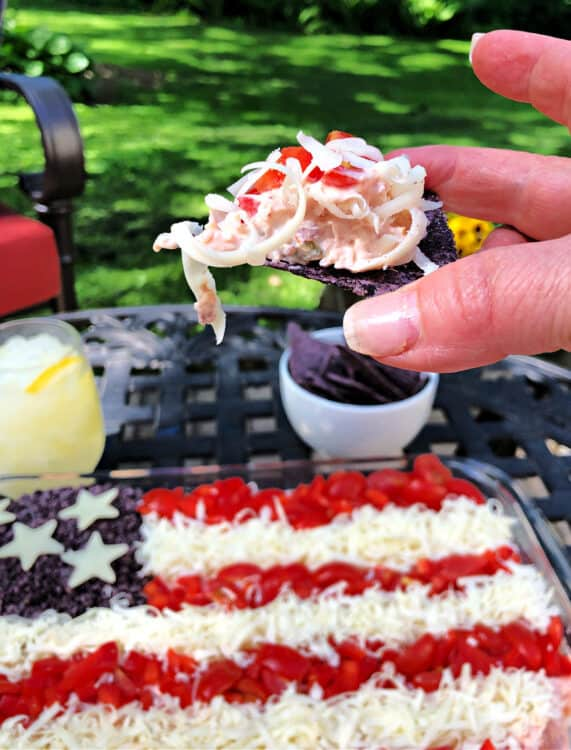 hand holding a chip covered in dip with whole pan of taco dip behind and outdoors