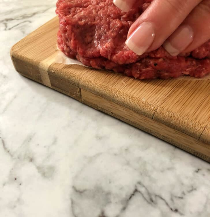 fingers sealing the edges of the 2 patties together