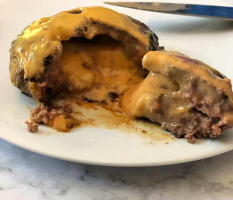 cut open juicy lucy showing hot lava effect of cheese oozing out