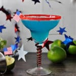 Blue margarita in a red rimmed glass, surrounded by garland stars and some limes