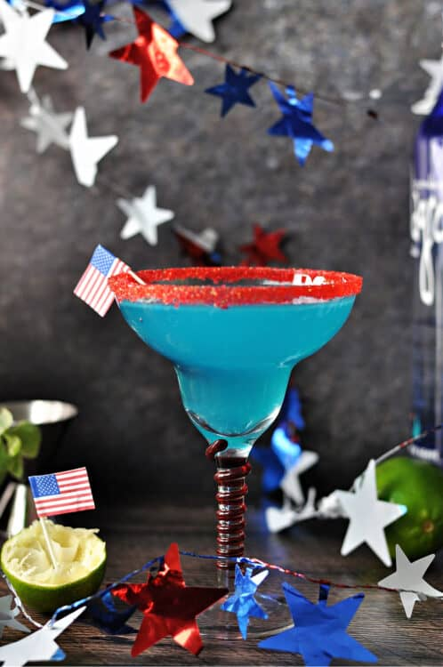 firecracker blue margarita in a red rimmed glass, surrounded by a garland of stars