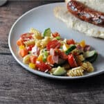 Easy pasta salad served on a plate with a brat in a bun