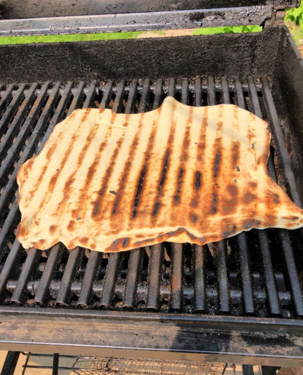 Crust flipped on the grill so the cooked side with grill marks is showing