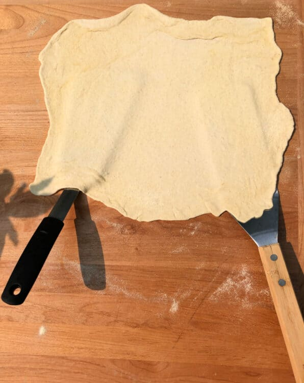 2 large spatulas picking up the rolled out dough