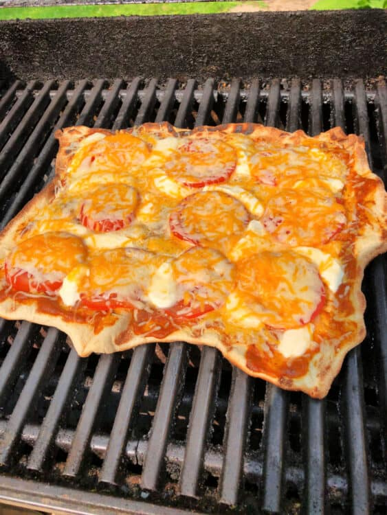 pizza on the grill, cheese is melted and ingredients are heated through
