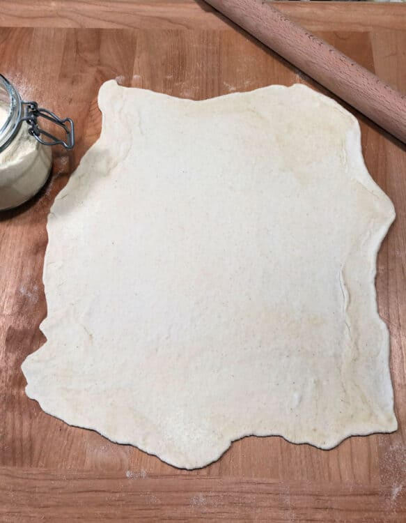 raw pizza dough rolled out on a cutting board