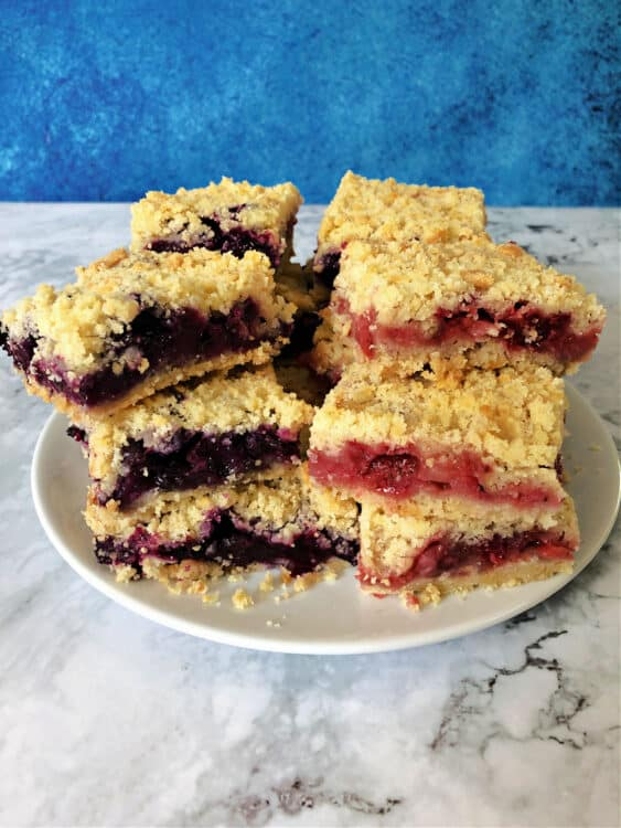 stack of berry crumble bars, blue version on the left and red version on the right