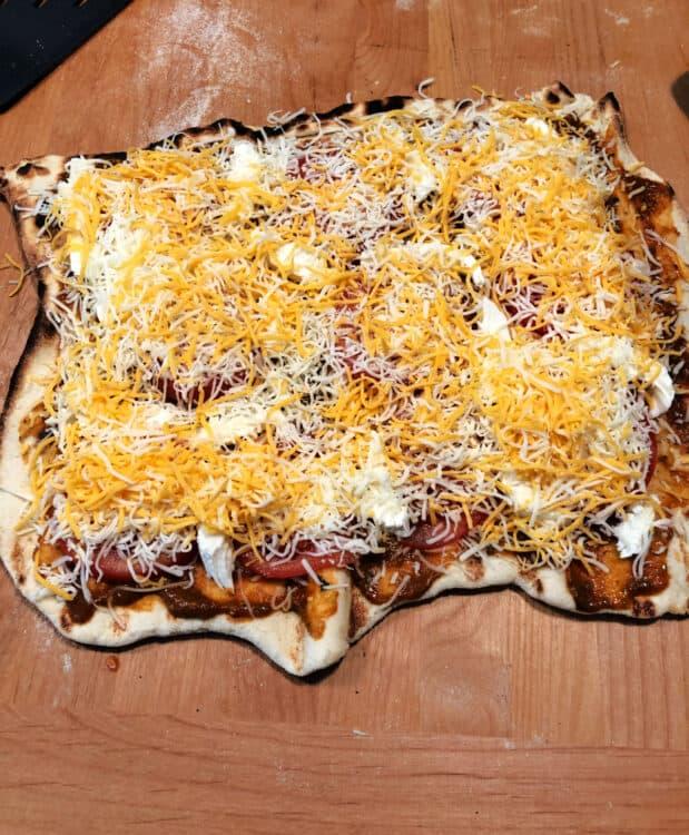 pizza crust on cutting board with toppings added