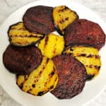 slices of grilled red and golden beets in an overlapping circle on a plate