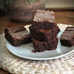 stack of brownies on a white plate with a plant behind