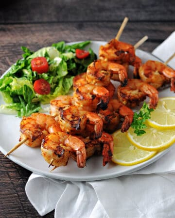 Grilled Cajun Shrimp on a plate with a small green salad and some lemon slices